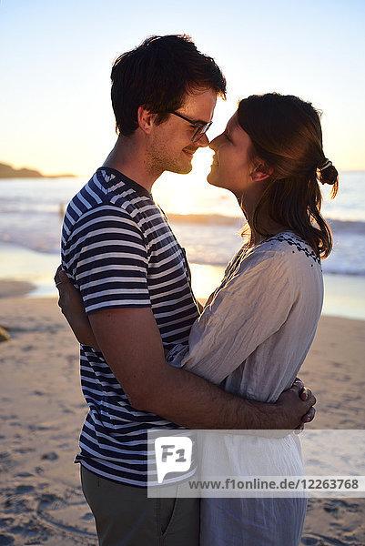 Romantisches Paar am Strand bei Sonnenuntergang
