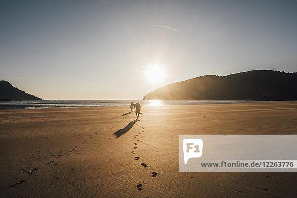 Kanada  British Columbia  Vancouver Island  zwei Männer  die bei Sonnenuntergang am Strand von San Josef Bay spazieren gehen.