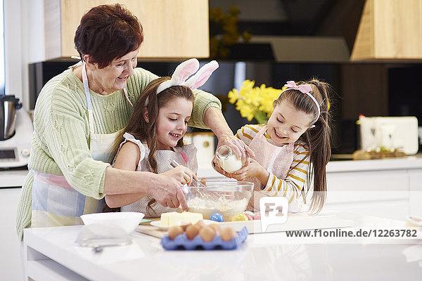 Großmutter und Enkelinnen backen gemeinsam Osterkekse in der Küche