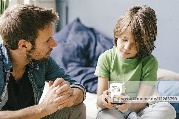 Vater schaut sich den Sohn an  der mit dem Würfel spielt.