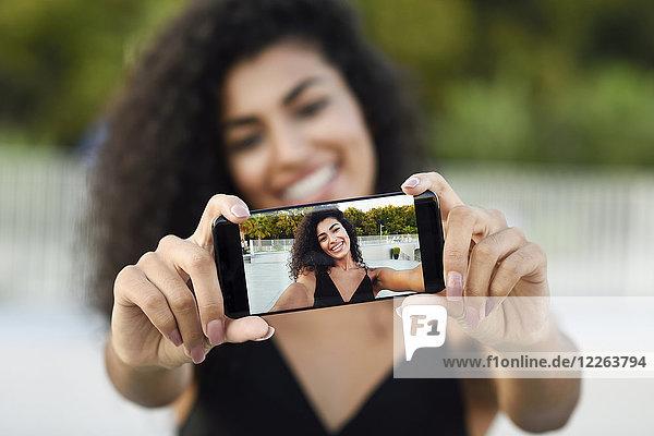 Glückliche junge Frau nimmt Selfie mit Handy  Nahaufnahme