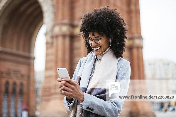 Spanien  Barcelona  glückliche Frau mit Handy und Kopfhörer am Tor