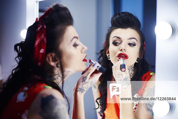 Spiegelbild einer tätowierten Frau mit rotem Lippenstift