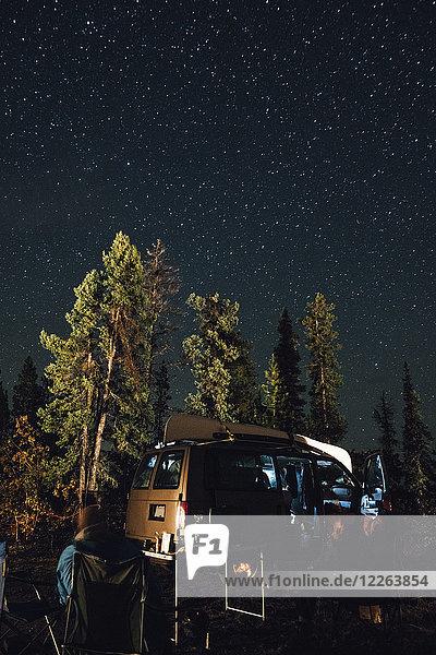 Kanada  British Columbia  zwei Männer sitzen nachts unter dem Sternenhimmel im Minivan.