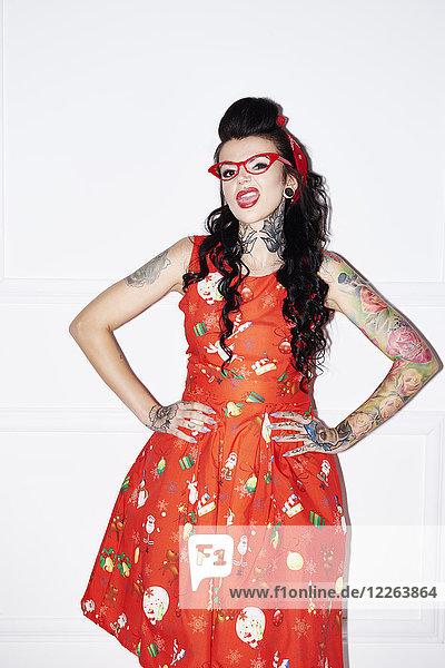 Portrait einer tätowierten Frau im gemusterten roten Kleid