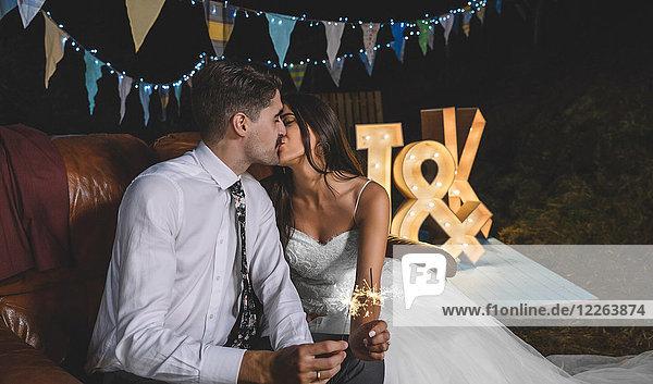 Romantisches Hochzeitspaar sitzt auf dem Sofa und küsst sich  während es auf einer Nachtparty im Freien Funkeln in den Händen hält.
