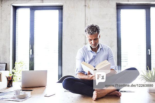 Der reife Geschäftsmann sitzt barfuß auf dem Schreibtisch im Büro und liest ein Buch.