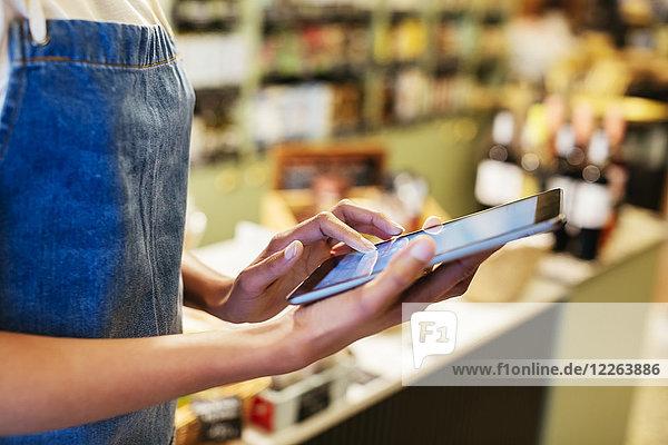Nahaufnahme einer Frau mit Tablette in einem Geschäft