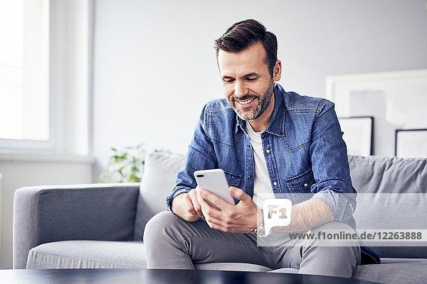 Lächelnder Mann auf dem Sofa sitzend mit dem Handy