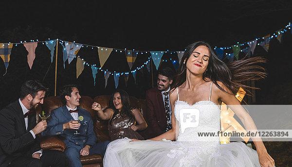 Fröhliches Brauttanzen auf einer nächtlichen Feldparty mit Bräutigam und Freunden im Hintergrund