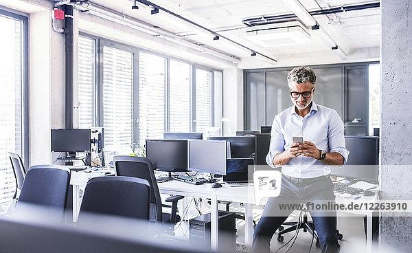 Lächelnder reifer Geschäftsmann sitzt auf dem Schreibtisch im Büro mit dem Smartphone