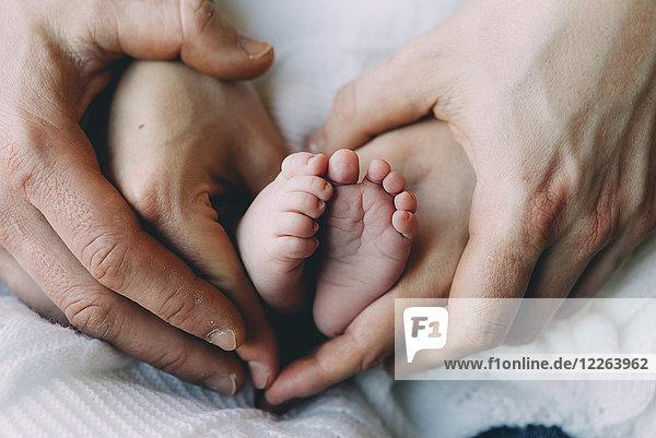 Die Hände des Vaters und der Mutter halten die Füße des Babys.