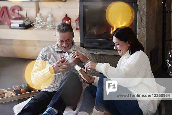 Happy mature couple at the fireplace unpacking gifts
