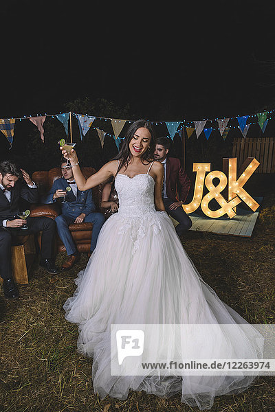 Happy bride holding cocktail glass on a night field party with groom and friends in the background