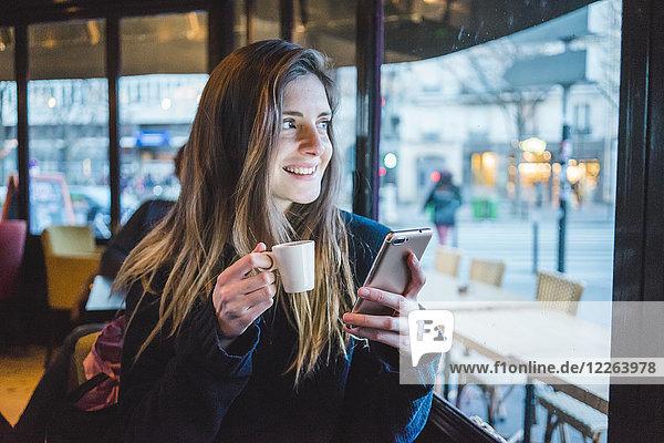 Paris  Frankreich  Porträt einer lächelnden jungen Frau mit Smartphone beim Espresso-Trinken in einem Café