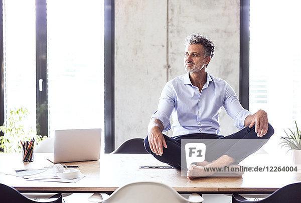 Der reife Geschäftsmann sitzt barfuß auf dem Schreibtisch im Büro.