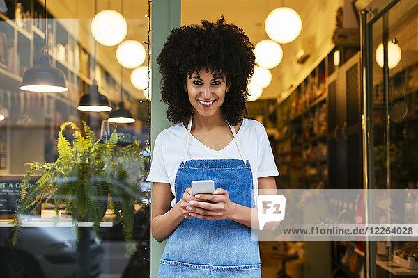 Porträt einer lächelnden Frau mit Handy in der Eingangstür eines Ladengeschäfts