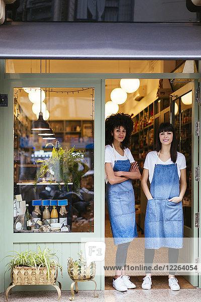 Porträt zweier lächelnder Frauen in der Eingangstür eines Ladens