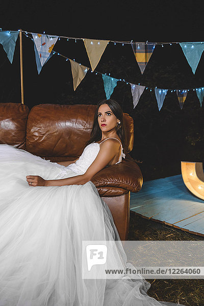 Serious bride lying on sofa on a night field party