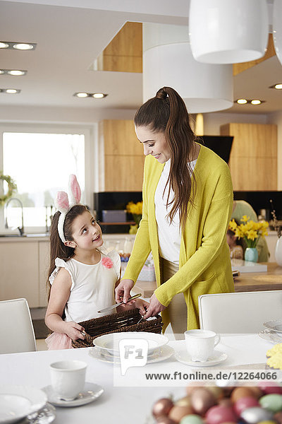 Smiling mother and daughter setting the table at home together