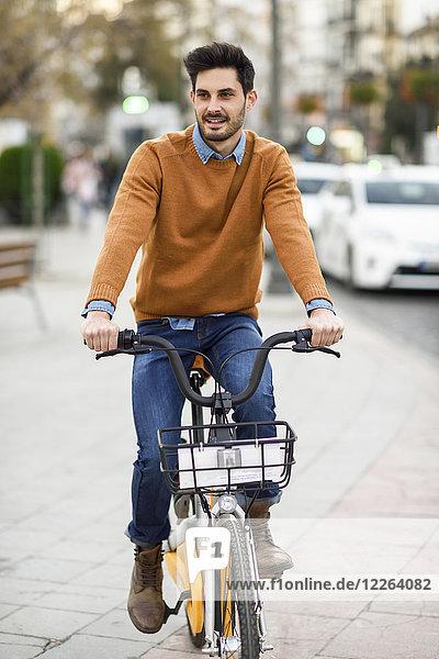 Portrait eines jungen Mannes  der in der Stadt Fahrrad fährt.
