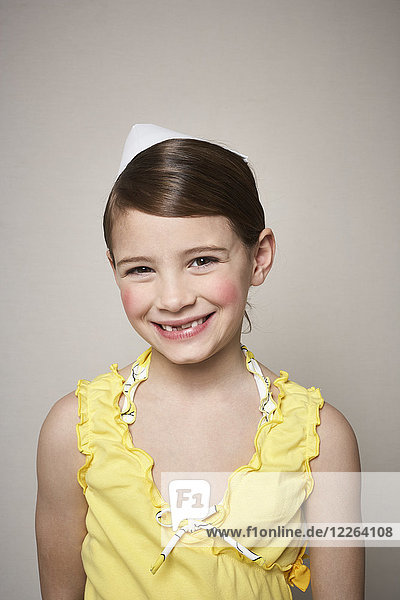 Portrait of grinning little girl with paper hat on her head