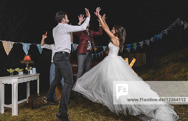 Happy bride jumping and giving high five with her friends on a night field party with friends