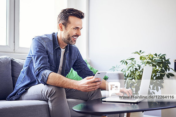 Smiling man sitting on sofa using laptop and cell phone