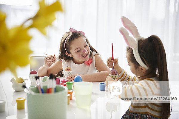 Schwestern sitzen am Tisch und malen Ostereier