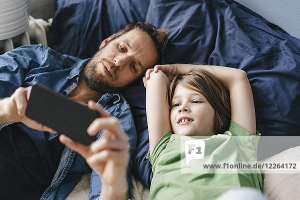 Vater und Sohn schauen gemeinsam zu Hause auf das Smartphone