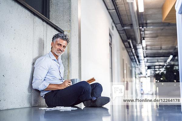 Porträt eines lächelnden  reifen Geschäftsmannes auf dem Boden sitzend