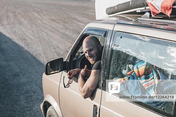 Porträt eines glücklichen jungen Mannes mit einem Minivan auf einem Roadtrip