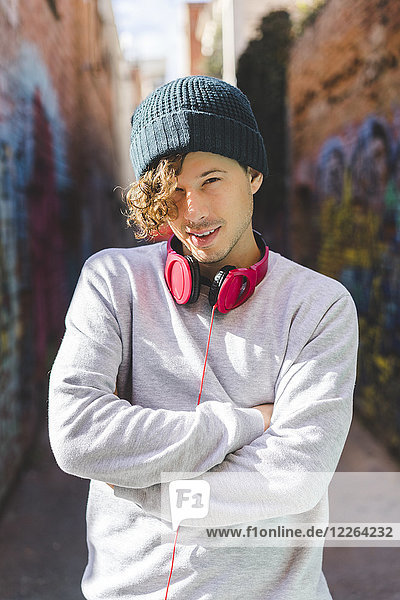 Portrait of young man with headphones wearing wool cap