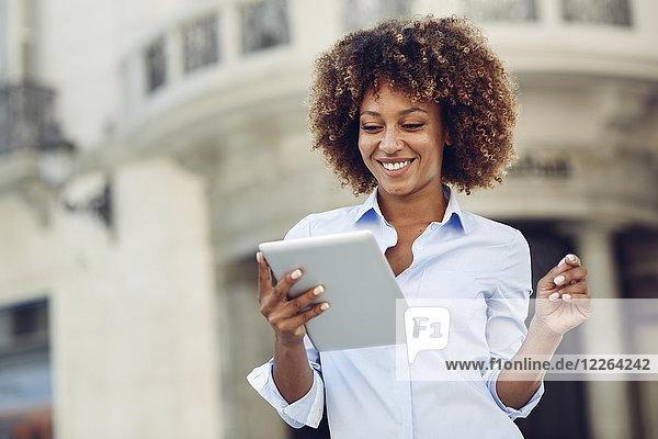 Lächelnde Frau mit Afro-Frisur mit Tablette in der Stadt