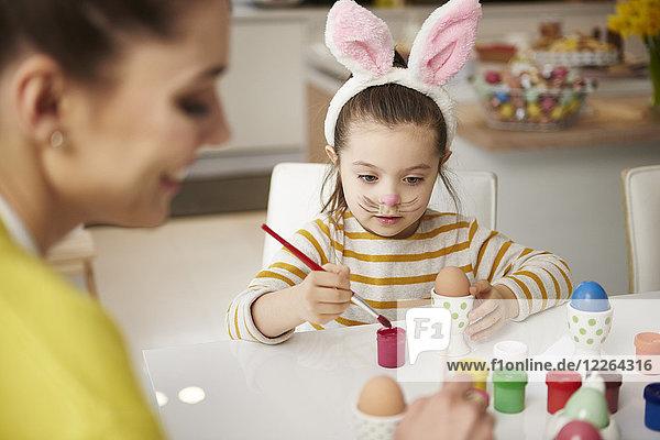 Mutter und Tochter mit Hasenohren sitzen am Tisch und malen Ostereier.