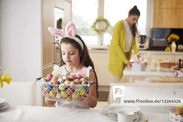 Girl placing basket full of Easter eggs on dining table