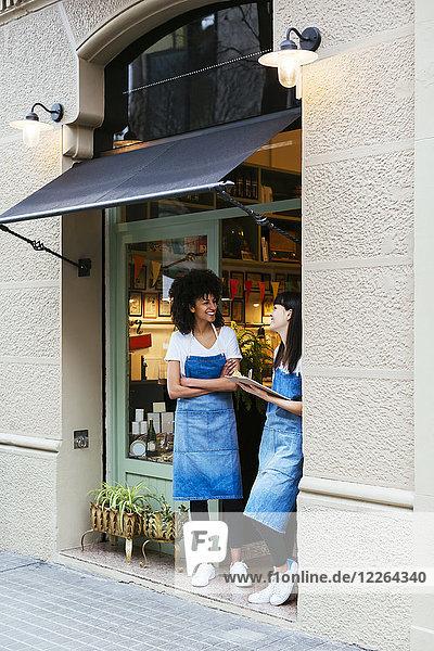 Zwei glückliche Frauen stehen in der Eingangstür eines Ladens.