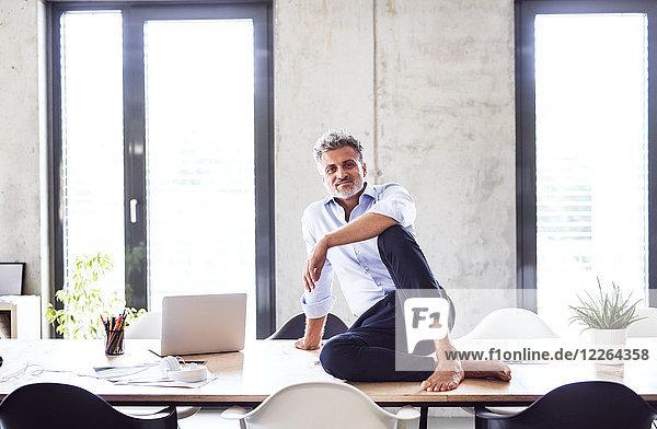 Porträt eines lächelnden  reifen Geschäftsmannes  der barfuß auf dem Schreibtisch im Büro sitzt.