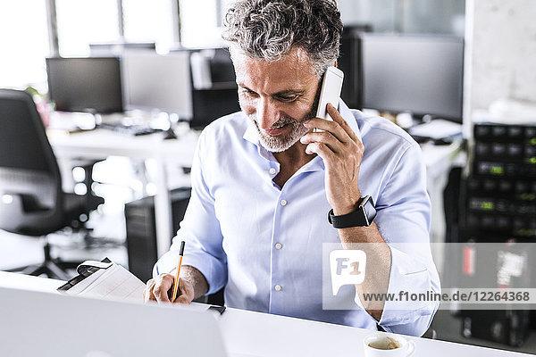 Lächelnder reifer Geschäftsmann sitzt am Schreibtisch im Büro und spricht auf dem Smartphone.