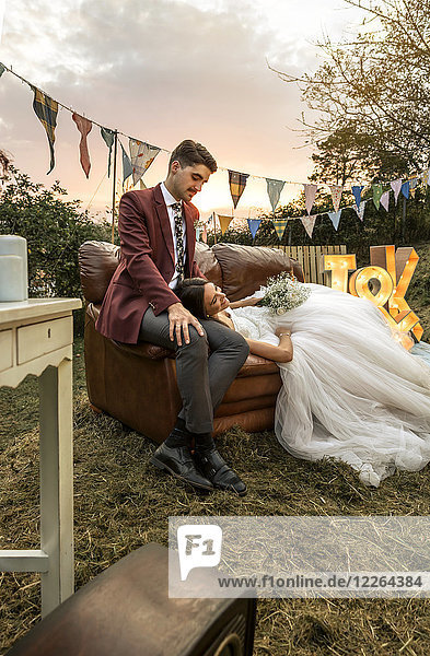 Bride lying over sofa with groom in the field