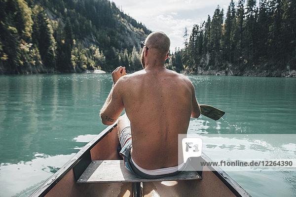 Kanada  British Columbia  nackter Mann im Kanu auf dem Kinbasket Lake