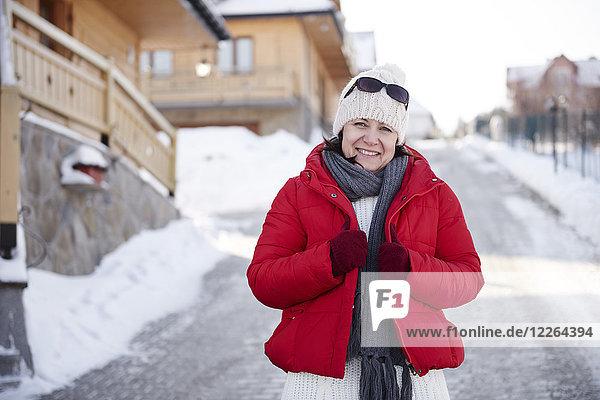 Porträt der lächelnden reifen Frau im Bergdorf im Winter