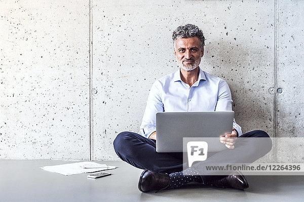 Porträt eines selbstbewussten  reifen Geschäftsmannes auf dem Boden sitzend mit Laptop