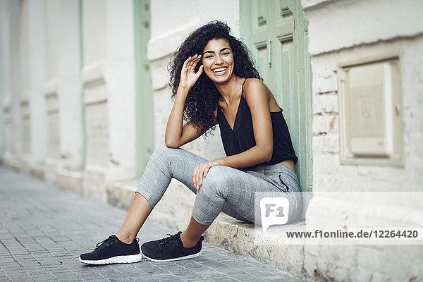 Porträt einer lachenden jungen Frau  die auf einer Stufe vor einer Eingangstür sitzt.