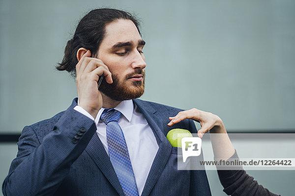 Geschäftsmann im Gespräch mit einer Frau  die einen Apfel in die Jackentasche steckt.