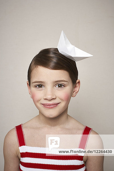 Portrait of smiling little girl with paper boat on her head