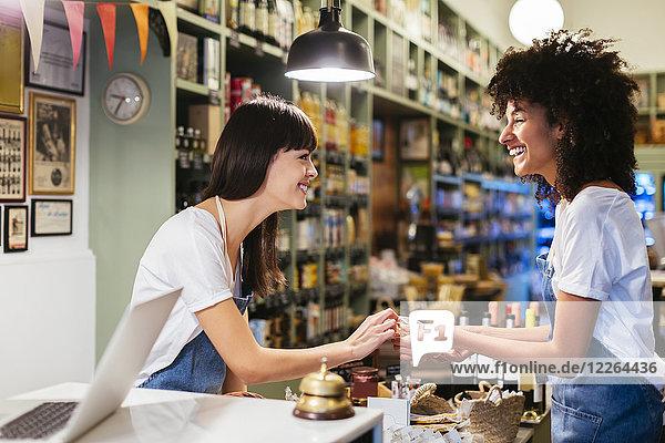 Zwei glückliche Frauen an der Theke in einem Laden