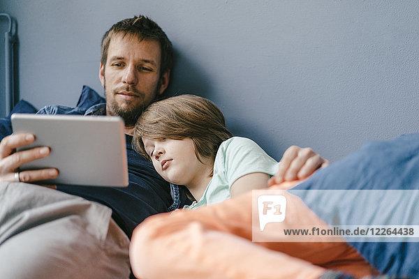 Vater und Sohn sehen sich zu Hause einen Film auf dem Tablett an.