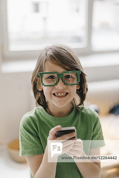 Porträt eines lächelnden Jungen mit einer Pixelbrille  der sein Handy hält.