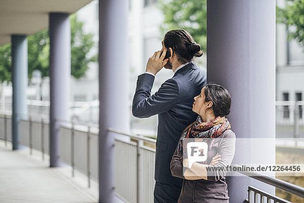 Frau schaut Geschäftsmann an  der am Handy spricht